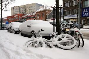 ondergesneeuwde auto en fietsen